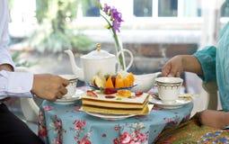 食用亚裔的商人茶和蛋糕和新鲜水果 库存照片