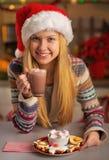 食用圣诞老人的帽子的少年圣诞节快餐 免版税库存照片