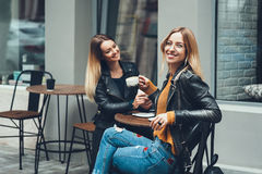 食用小组欧洲的女孩咖啡一起 咖啡馆的两名妇女谈话,笑,说闲话和享受他们的时间的 免版税图库摄影