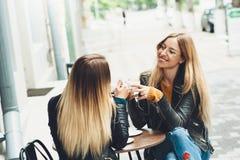 食用小组美丽的女孩咖啡一起 免版税图库摄影