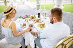 食用年轻的夫妇浪漫早餐户外 图库摄影