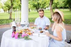食用年轻的夫妇浪漫早餐户外 免版税图库摄影