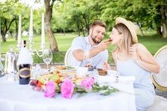 食用年轻的夫妇浪漫早餐户外 库存图片