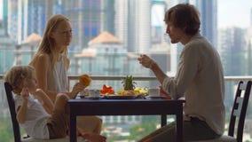 食用年轻的家庭早餐,在他们的阳台的午餐在一个摩天大楼有在城市的整体街市的一个看法 股票录像