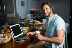 食用微笑的人咖啡,当使用膝上型计算机在柜台时 图库摄影