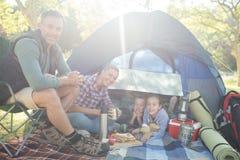 食用微笑的家庭在帐篷之外的快餐在一个晴天 库存图片