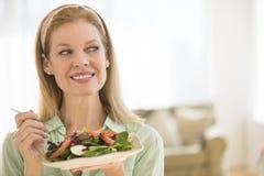 食用微笑的成熟的妇女沙拉在家 免版税库存图片