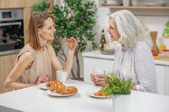 食用快乐的妇女与父母的早餐 免版税库存照片