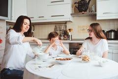 食用愉快的家庭早餐在家 有吃早晨的两个孩子的母亲在现代白色厨房里 图库摄影