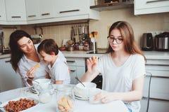 食用愉快的家庭早餐在家 有吃早晨的两个孩子的母亲在现代白色厨房里 免版税图库摄影