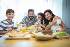 食用愉快的家庭画象早餐一起 库存照片