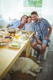 食用愉快的家庭画象早餐一起 库存图片