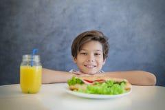 食用愉快的青少年的男孩早餐在家 图库摄影