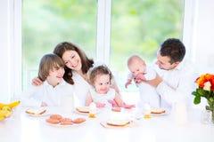 食用愉快的年轻的家庭乐趣早餐 库存图片