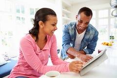 食用早餐和使用数字式片剂的夫妇在厨房 免版税库存照片