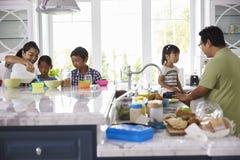 食用早餐和做午餐的家庭在厨房 免版税库存照片