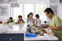 食用早餐和做午餐的家庭在厨房 库存照片