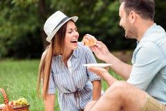 食用松弛早餐在公园,吃新月形面包和喝咖啡的愉快的年轻夫妇 库存图片