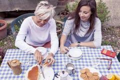 食用母亲和成人的女儿早餐 免版税图库摄影