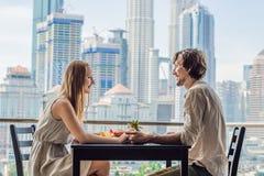 食用爱恋的夫妇在阳台的早餐 早餐桌用咖啡果子和面包croisant在阳台反对backd 免版税库存照片