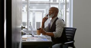 食用的商人咖啡,当谈话在输送路线和使用膝上型计算机在书桌4k时 股票录像
