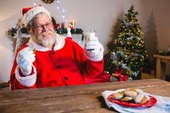 食用的圣诞老人与杯的一个曲奇饼牛奶 库存照片