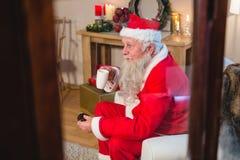 食用的圣诞老人坐和咖啡 免版税库存照片