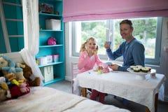 食用的女孩和的父亲从被设置的玩具厨房的茶 库存照片