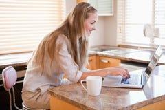 食用的妇女咖啡,当使用笔记本时 免版税库存图片