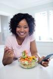 食用的妇女沙拉,当使用手机时 库存照片