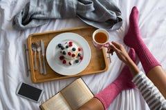 食用的妇女的低部分在床上的早餐 免版税库存图片