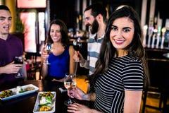 食用的妇女画象与朋友的一个开胃酒 库存图片