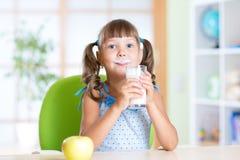 食用的小女孩早餐:喝玻璃  免版税库存图片