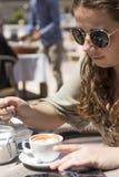 食用的少女一份咖啡在一个晴朗的春日 库存图片