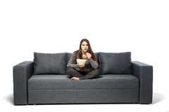 食用的少妇玉米花,当享受电影坐沙发时 免版税库存照片