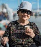 食用的帽子的资深妇女一杯咖啡 免版税库存图片
