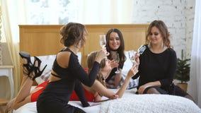 食用的晚礼服的发光的女孩在床上的乐趣和饮料香槟 股票录像