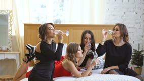 食用的晚礼服的发光的女孩在床上的乐趣和饮料香槟 股票视频