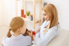 食用的母亲和的女儿在沙发的茶 库存照片