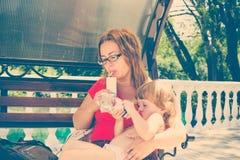 食用的母亲和的女儿早餐户外 库存图片