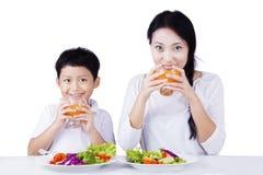 食用的母亲和的孩子在演播室的早餐 免版税库存照片