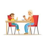 食用的祖母与男孩,获得一部分的早餐的祖父母与孙系列的乐趣 库存例证