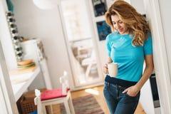 食用美丽的白肤金发的妇女早晨咖啡在家 免版税库存图片
