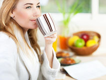 食用美丽的镇静的少妇早晨咖啡 图库摄影