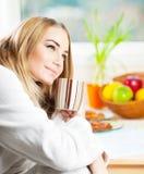 食用美丽的镇静的少妇早晨咖啡 免版税库存图片