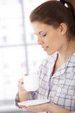 食用轻松的妇女早晨咖啡 免版税库存图片
