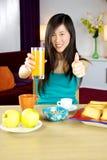 食用逗人喜爱的亚裔的妇女健康早餐用果子和橙汁 库存照片