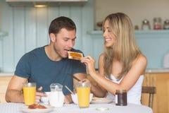 食用逗人喜爱的夫妇早餐一起 免版税库存照片
