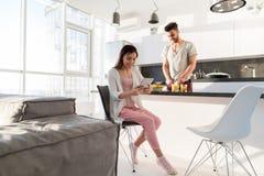 食用年轻的夫妇早餐,使用片剂计算机西班牙人的亚裔妇女烹调食物厨房 库存照片