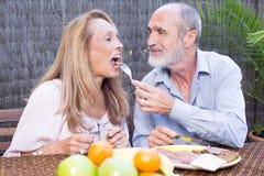 食用年长的夫妇在大阳台的食物 免版税库存图片